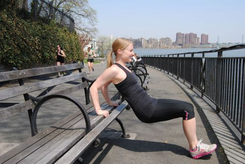 Woman doing tricep dips on a park bench.