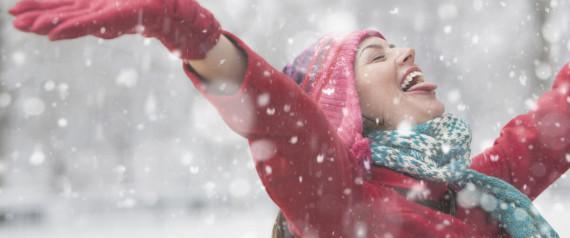 Woman in falling snow feeling wonderful.