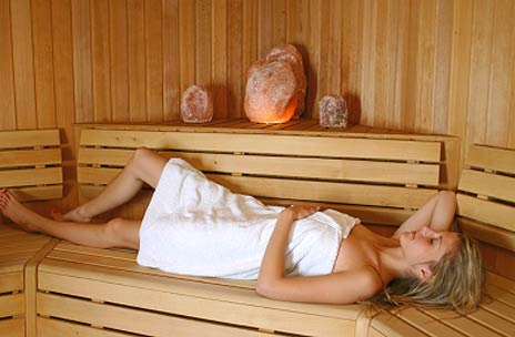 Person relaxing in sauna.